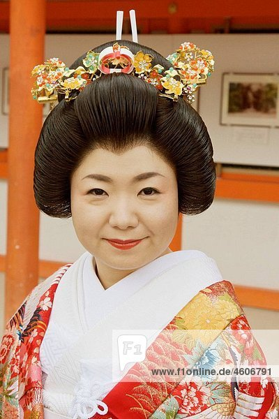 A just married Japanese bride wearing a traditional wedding kimono  traditional hair style and hair piece in Shimogamo shrine in Kyoto