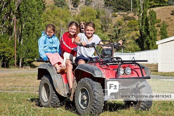 Upcot Station girls with pet spaniel ride quad bike on farm  Upper Awatere valley  Marlborough  New Zealand.