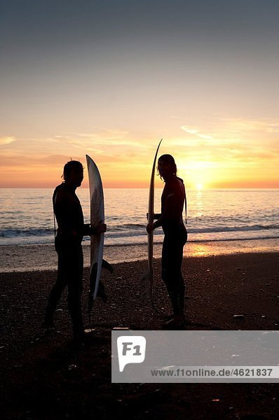 Two young men surfing at sunset off Aberystwyth beach  Wales UK