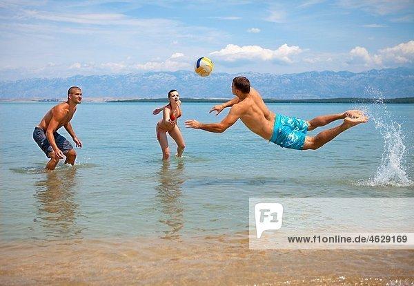 Kroatien  Zadar  Freunde spielen Volleyball am Strand