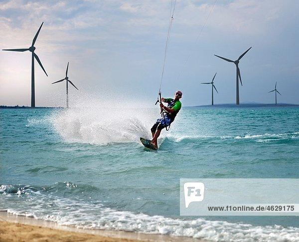 Kroatien  Zadar  Kitesurfer springen vor der Windkraftanlage