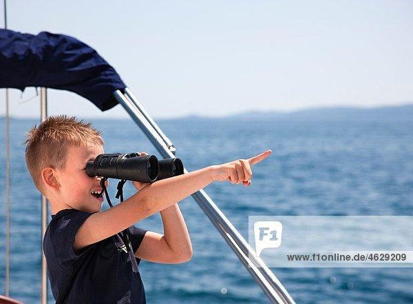 Kroatien  Zadar  Junge sucht durch ein Fernglas vom Segelboot aus