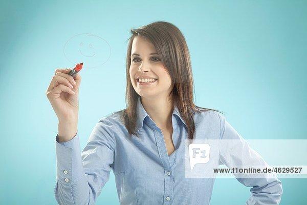 Geschäftsfrau beim Zeichnen an Bord  lächelnd