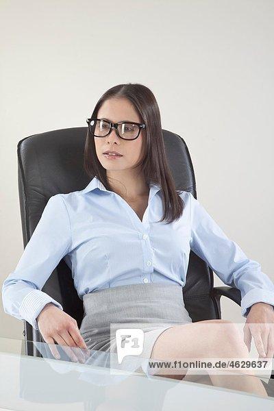 Geschäftsfrau auf Stuhl im Büro  wegschauend