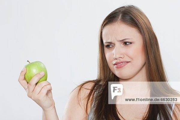 Junge Frau schaut auf grünen Apfel