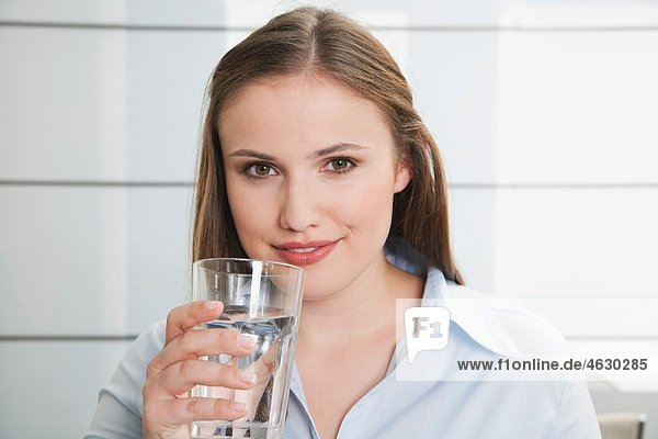 Young woman with glass of water  smiling  portrait