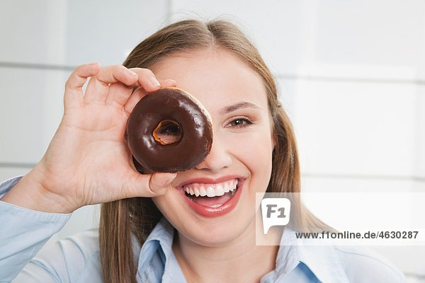 Junge Frau schaut durch den Donut  lächelnd  Portrait