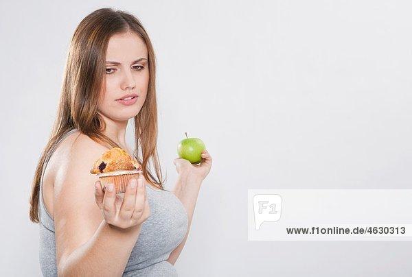 Junge Frau mit Tasse Kuchen und grünem Apfel