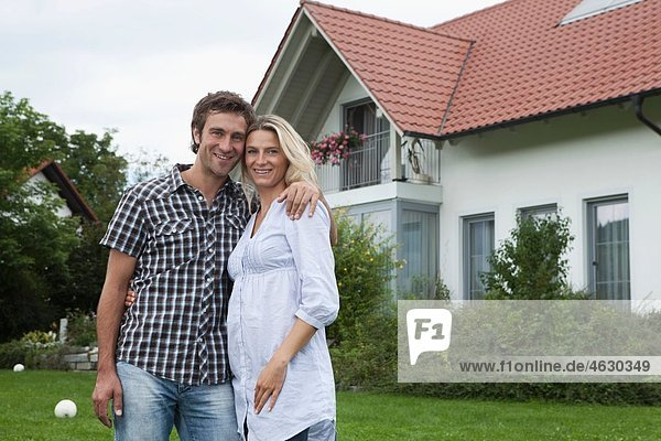 Deutschland  München  Paar vor dem Haus stehend  lächelnd  Portrait