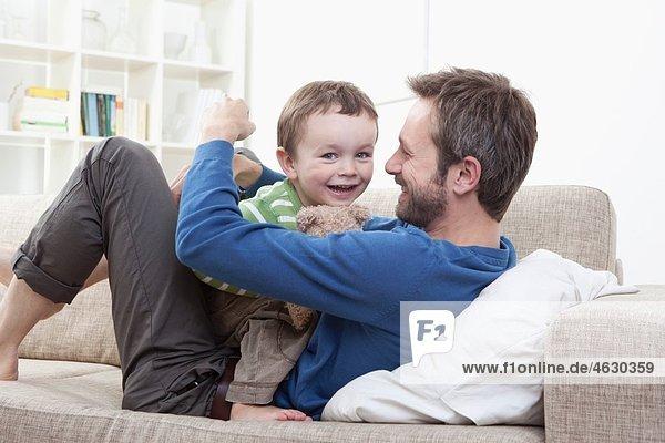 Deutschland  Bayern  München  Vater und Sohn (2-3 Jahre) mit Spaß auf dem Sofa
