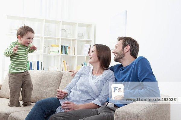 Deutschland  Bayern  München  Sohn (2-3 Jahre) spielt vor den Eltern im Wohnzimmer