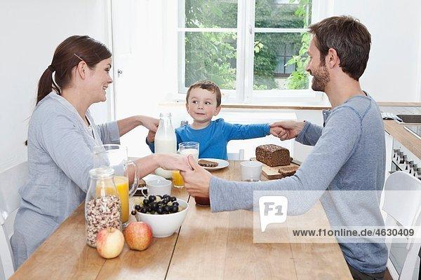Deutschland  Bayern  München  Familie beim gemeinsamen Frühstücken