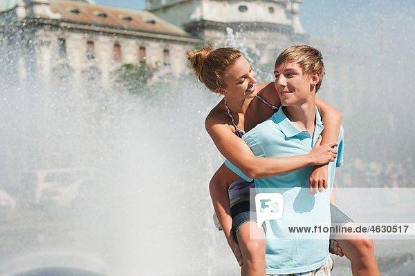 Junger Mann mit Frau auf Huckepack
