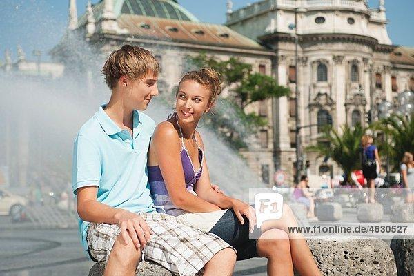 Junger Mann und Frau am Brunnen sitzend