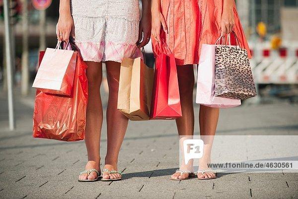 Junge Frauen warten mit Einkaufstaschen auf dem Fußweg