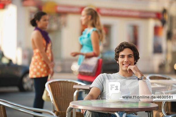 Junger Mann im Café lächelt mit Freunden im Hintergrund