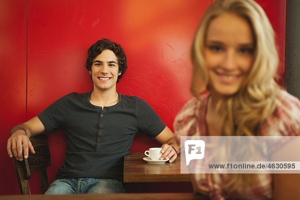 Young man smiling with teenage girl in foreground