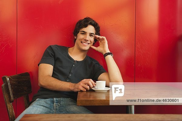 Young man in cafe  smiling  portrait