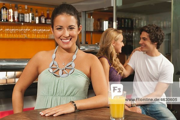 Young woman smiling with couple in background