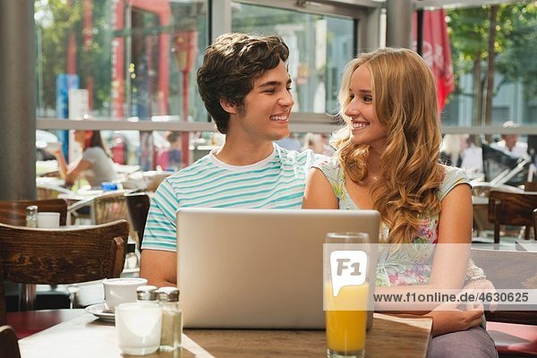 Germany  Munich  Couple with laptop in cafe