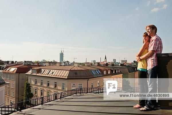 Deutschland  Bayern  München  Junges Paar auf dem Dach mit Stadt im Hintergrund