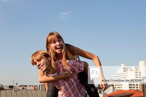 Deutschland  Bayern  München  Junges Paar genießt auf dem Dach