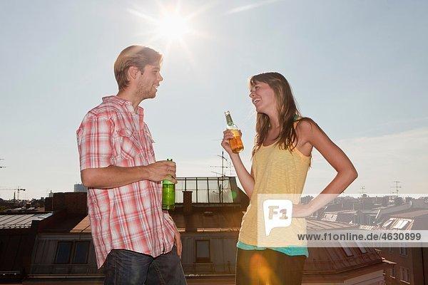 Deutschland  Bayern  München  Junges Paar im Gespräch und Biergenuss auf dem Dach