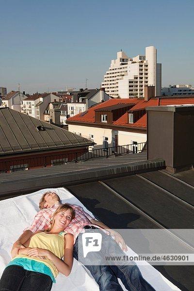 Deutschland  Bayern  München  Junges Paar entspannt auf dem Dach