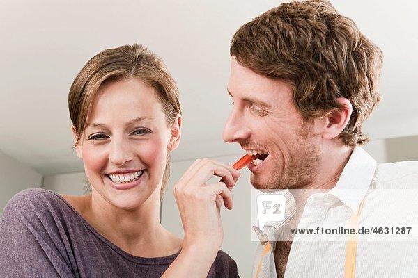 Frau füttert den Mann mit einer Scheibe Paprika