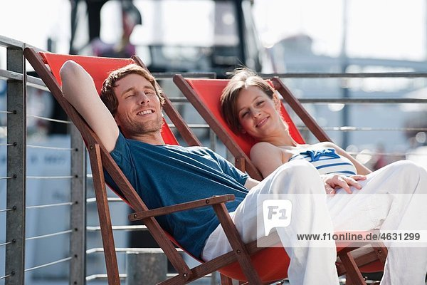 Germany  Hamburg  Couple relaxing in deck chair on floating home