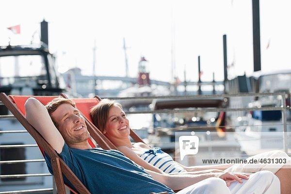 Deutschland  Hamburg  Paar im Liegestuhl entspannen  lächeln