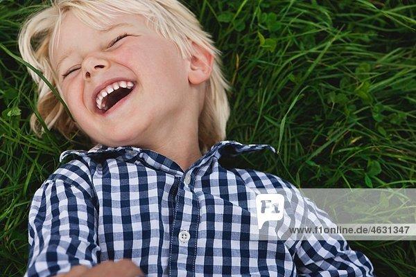 Junge (2-3 Jahre) auf Gras liegend und lachend