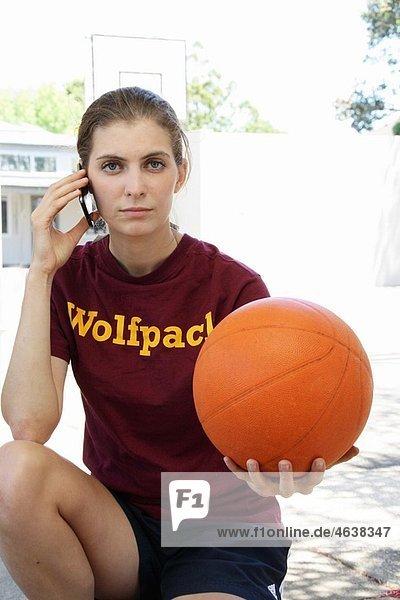woman talking on phone holding basketball