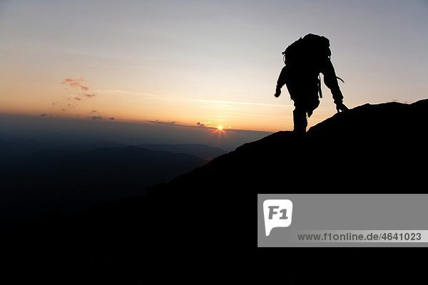 A hiker travels along the Appalachian Trail at sunset near Moun Washington in the White Mountains,  New Hampshire USA Notes: Mount Washington is famous for the highest wind gust ever measured on earth at 231 miles per hour on April 12,  1934