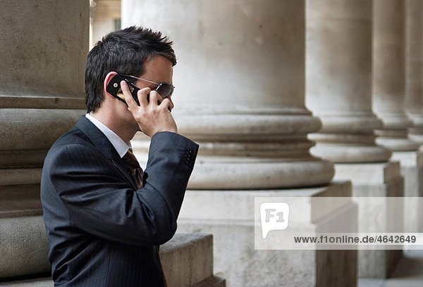 Young businessman luses mobile phone in the City of London,  outside the Royal Exchange,  UK