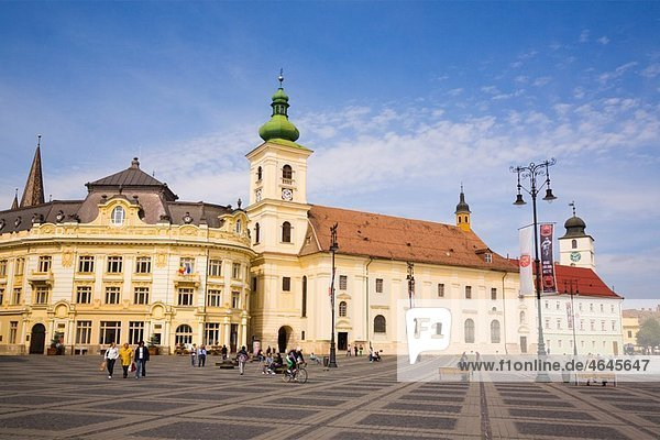 Sibiu Transylvania Romania Europe Roman Catholic church of the Holy Trinity and old buildings in Piata Mare pedestrianised square in historic city centre of Hermannstadt