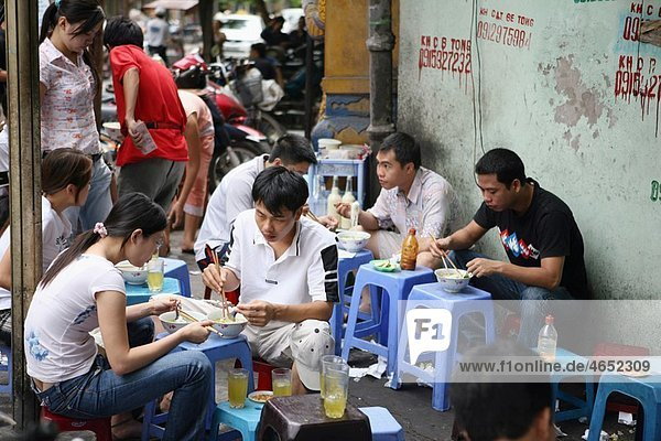 Group of people sitting together and eating food in the street  Hanoi  Vietnam