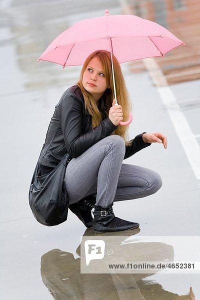 Under pink umbrella young woman