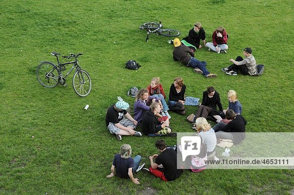 Young people sit talking in a park