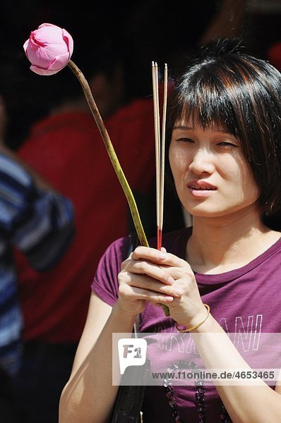Singapore: a Chinese woman praying at the Goddess of Mercy Temple