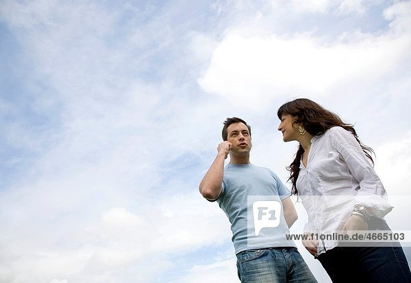 Male chatting on mobile with female looking on