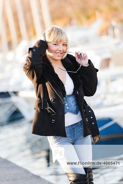 Posing in front of numerous boats with glasses in her hand handsome young woman
