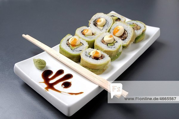 Sushi on a platter with chopsticks