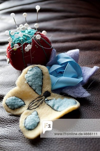 A tomato pin cushion and a flower and butterfly sewn by hand