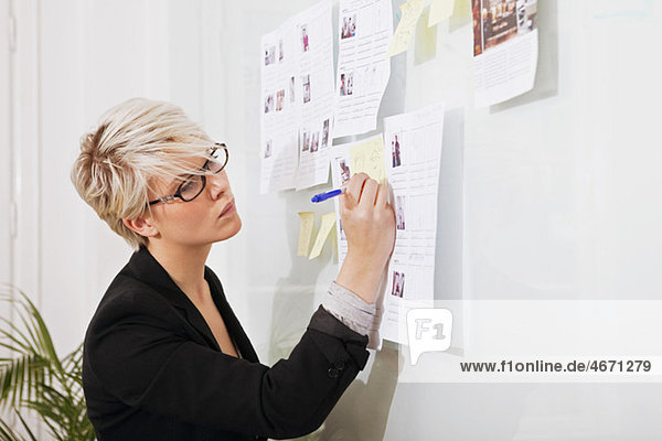 Woman writing on paper that hangs on wall