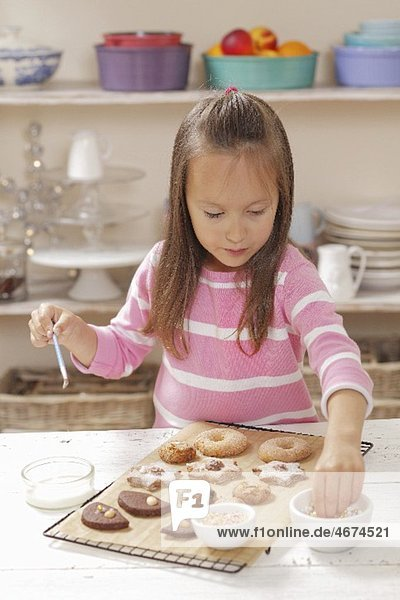 Mädchen verziert Plätzchen mit Zuckerperlen