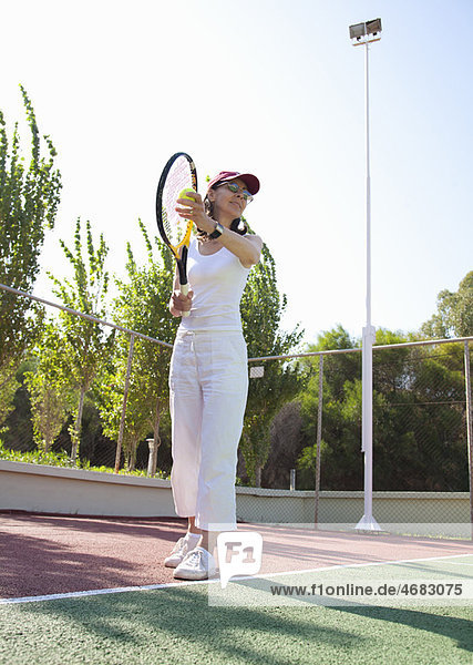 Woman playing tennis  about to serve