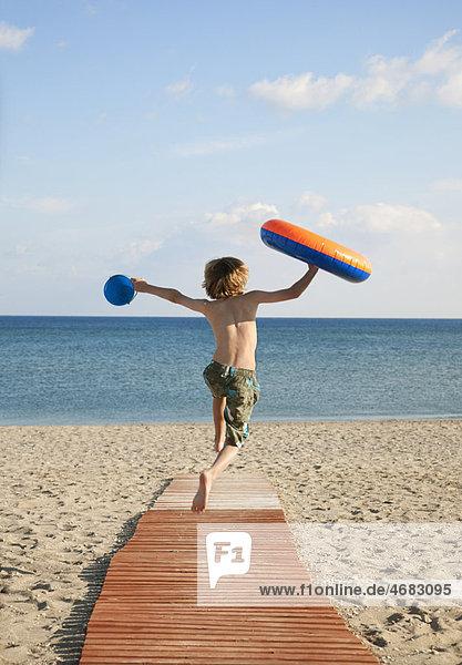 Junge (8-9) rennt die Uferpromenade hinunter zum Meer