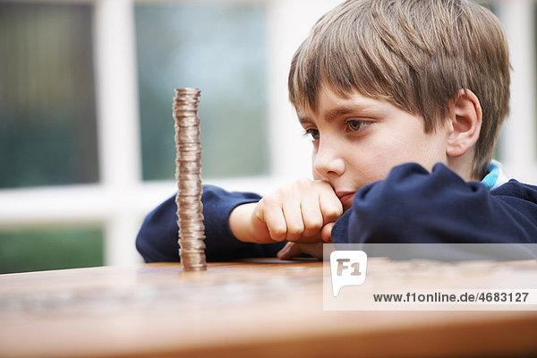Junge schaut auf einen Münzenturm