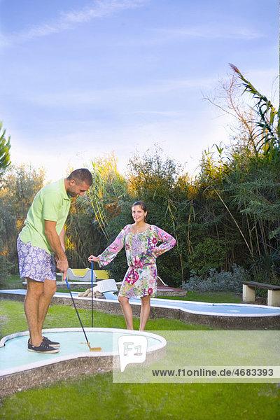 Paare spielen Minigolf